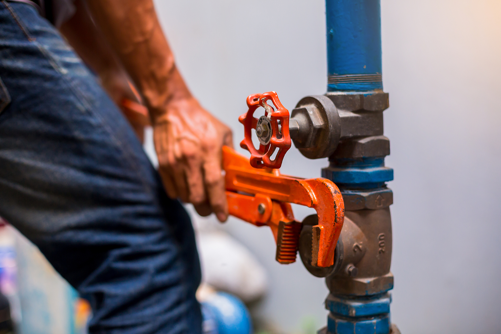 Plumber using a wrench to repair and remove the water supply pipe and valve.