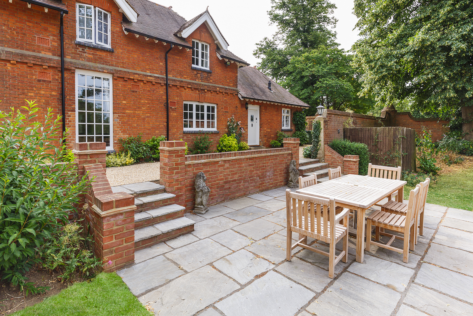 Large historic Victorian house featuring a garden and patio with reclaimed teak furniture.