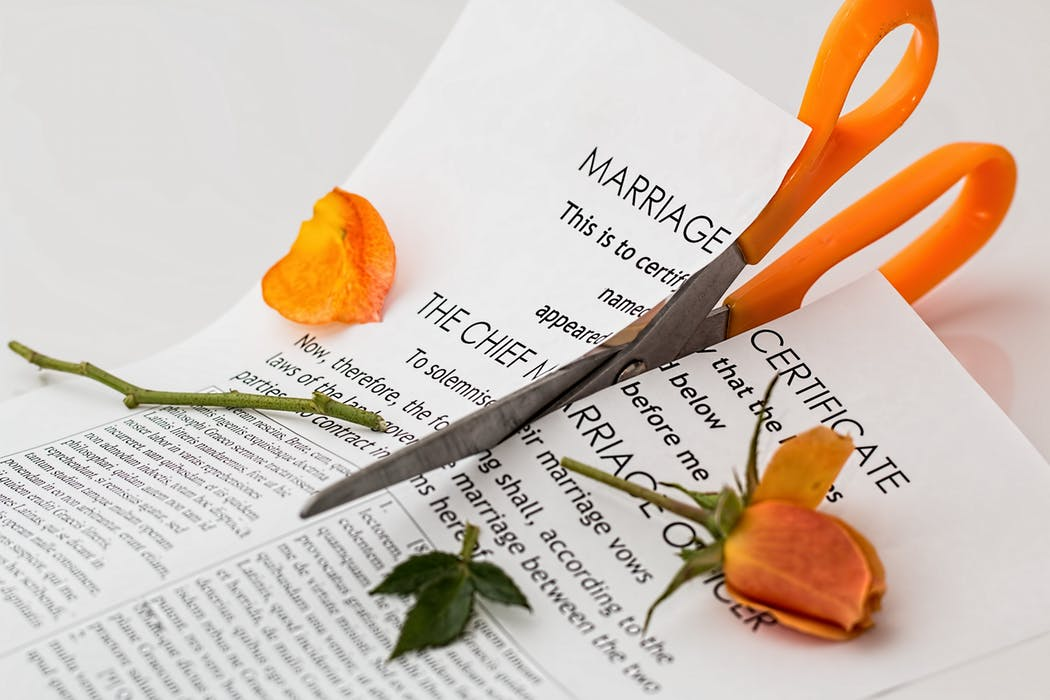 marriage certificate being torn apart. Diivorce concept