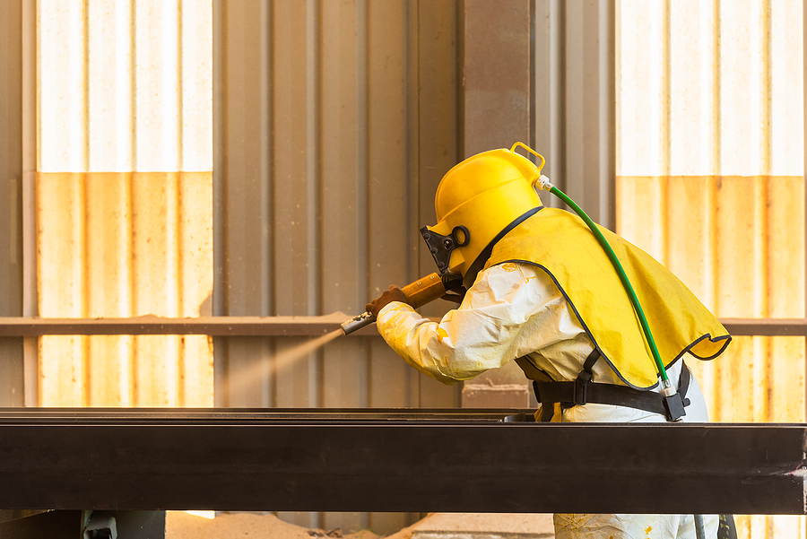 Worker in protective suit while doing grit blasting