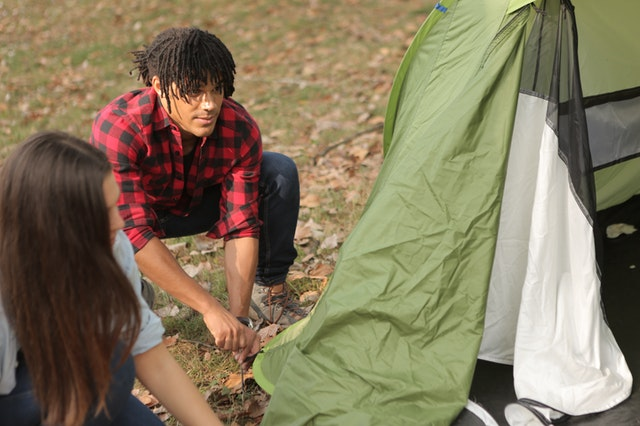 Couple assembling a camping tent