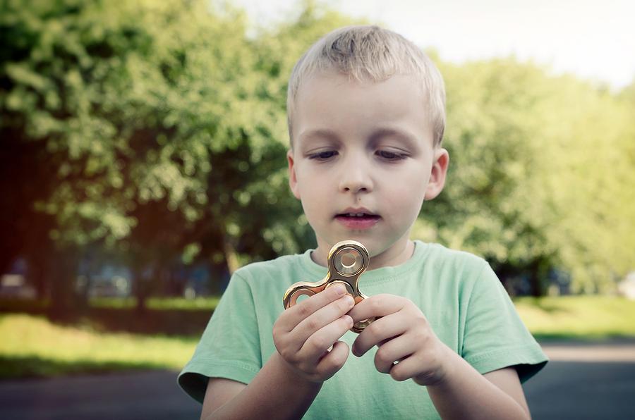 Little boy with a fidget spinner outdoors.